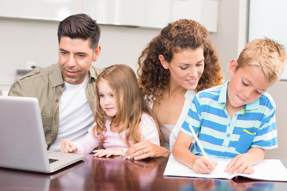 """""""Cheerful parents colouring and using laptop with their children"""" stock image"""