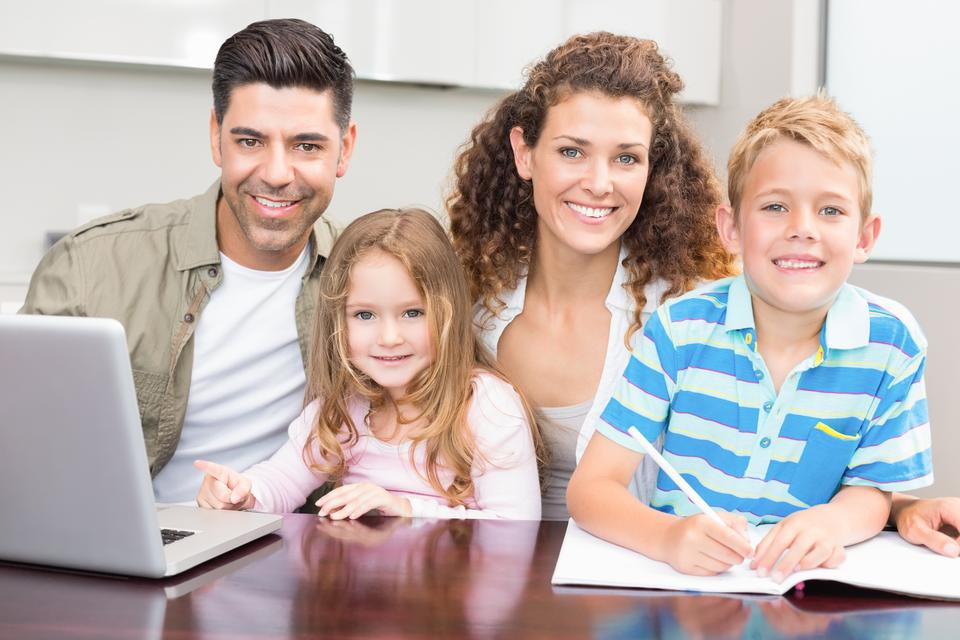 """""""Happy parents colouring and using laptop with their young children"""" stock image"""
