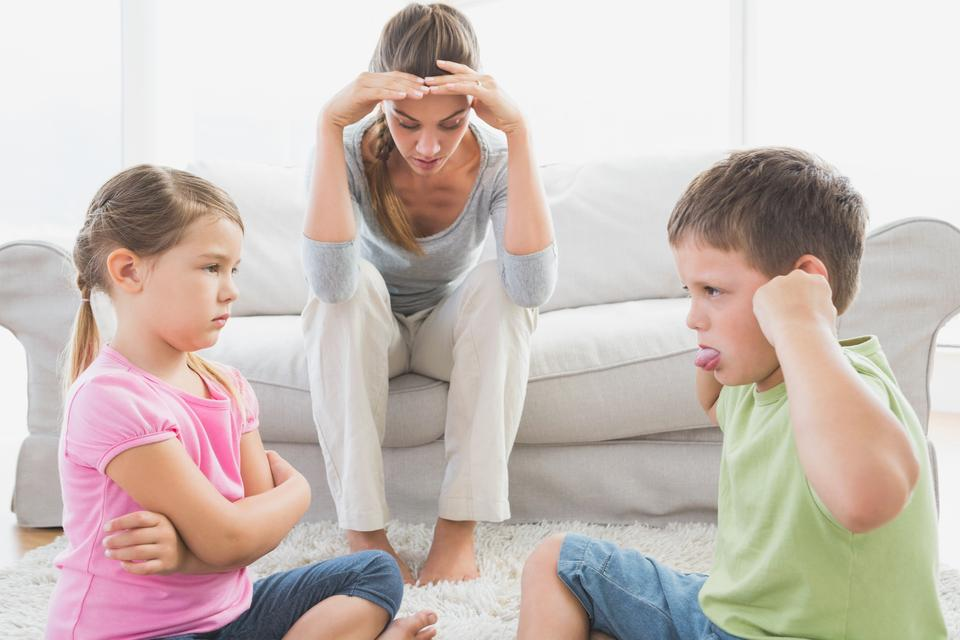 """""""Fed up mother listening to her young children fight"""" stock image"""