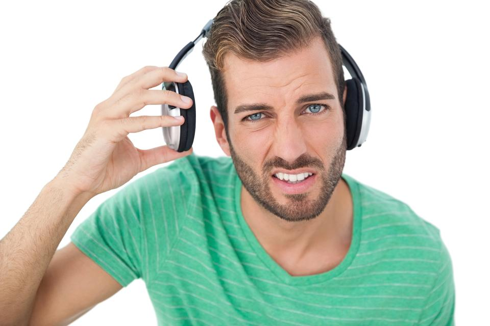 """Portrait of a irritated young man with headphones"" stock image"