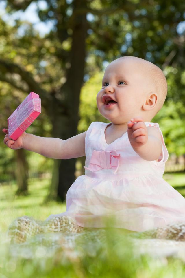 """""""Cute happy baby holding with a box at park"""" stock image"""