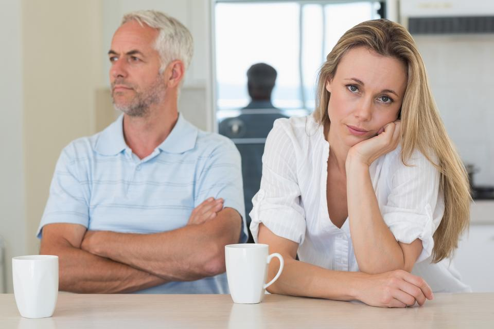 """""""Fed up woman sitting at the counter with her partner"""" stock image"""