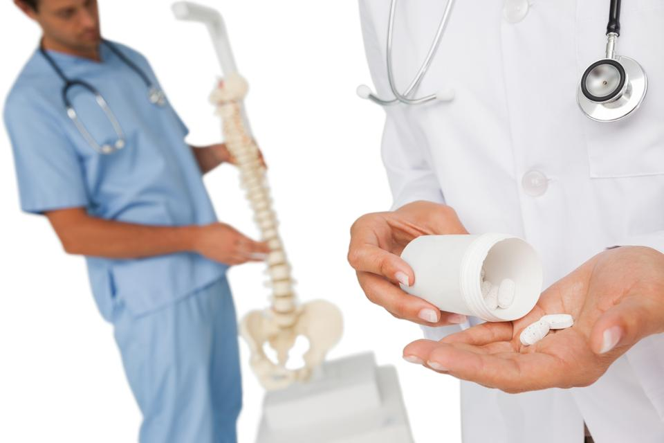 """Mid section of female doctor with pills and skeleton model"" stock image"