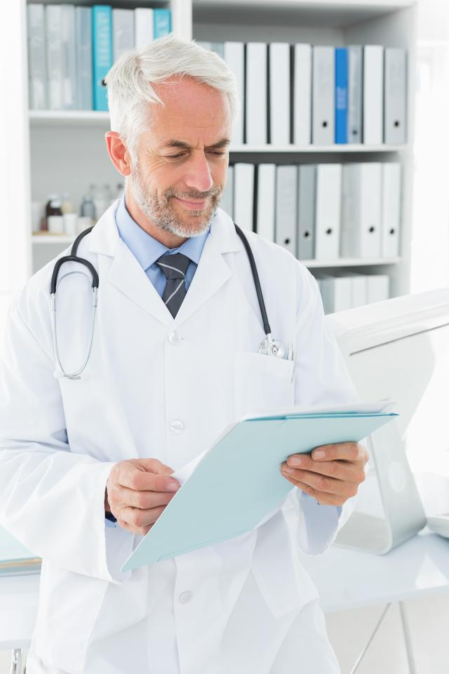 """""""Doctor looking at a folder in the medical office"""" stock image"""