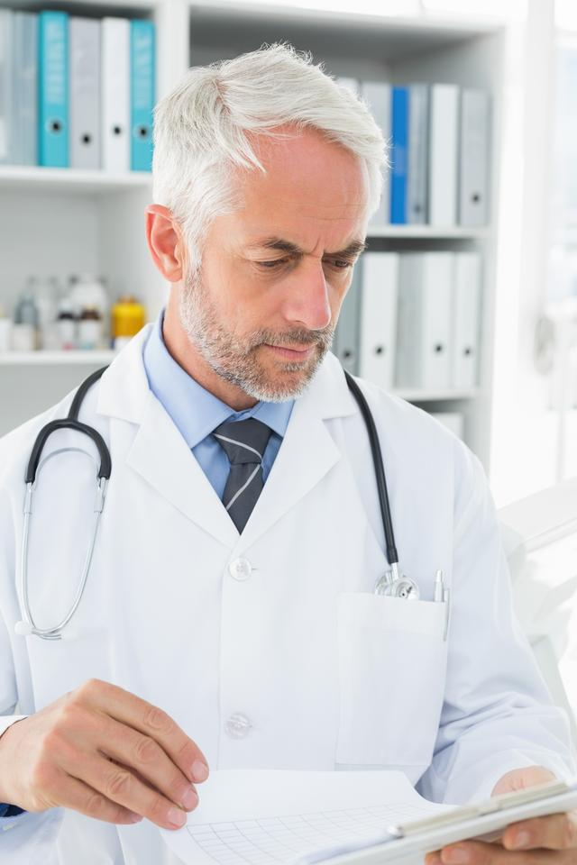 """""""Doctor looking at reports in the medical office"""" stock image"""