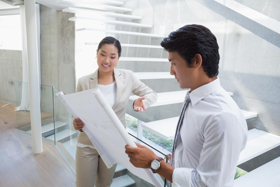 """""""Estate agent looking at blueprint with potential buyer"""" stock image"""