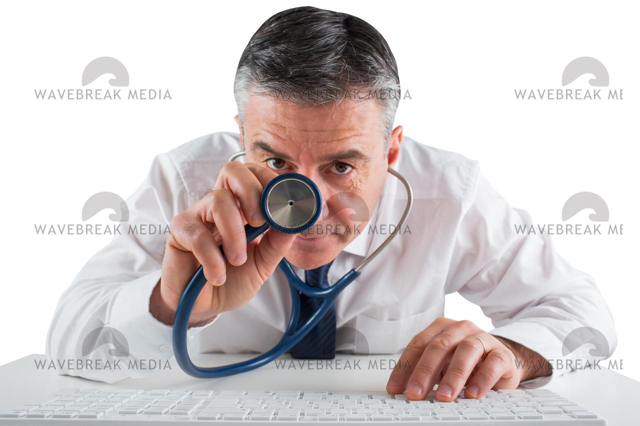 """Mature businessman running diagnostics with stethoscope"" stock image"