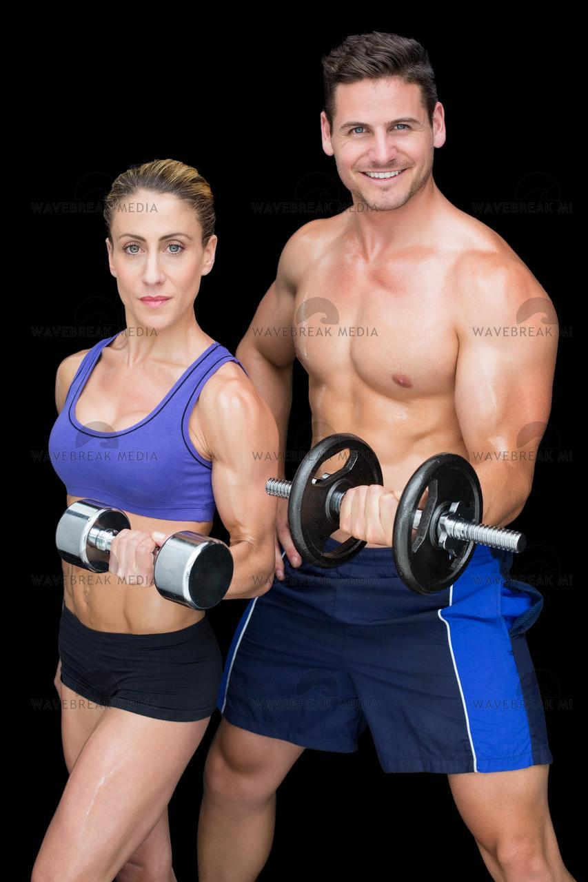 """""""Crossfit couple posing with dumbbells smiling at camera"""" stock image"""