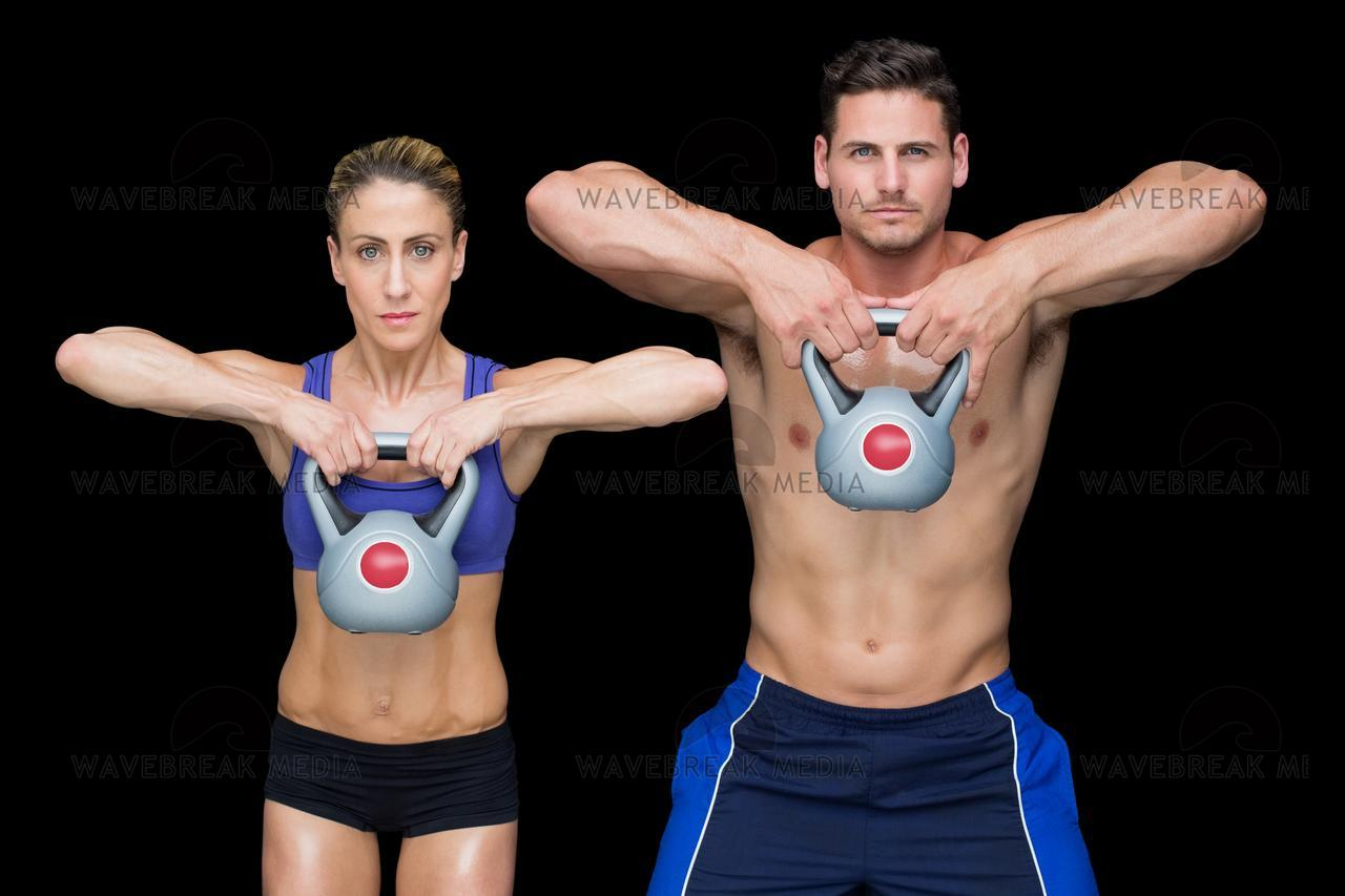 """""""Crossfit couple posing with kettlebells"""" stock image"""