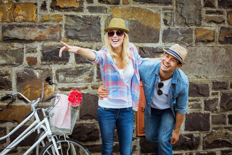 """""""Hip young couple standing by brick wall with their bikes"""" stock image"""