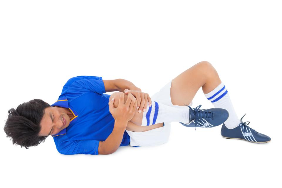 """Football player in blue lying injured"" stock image"
