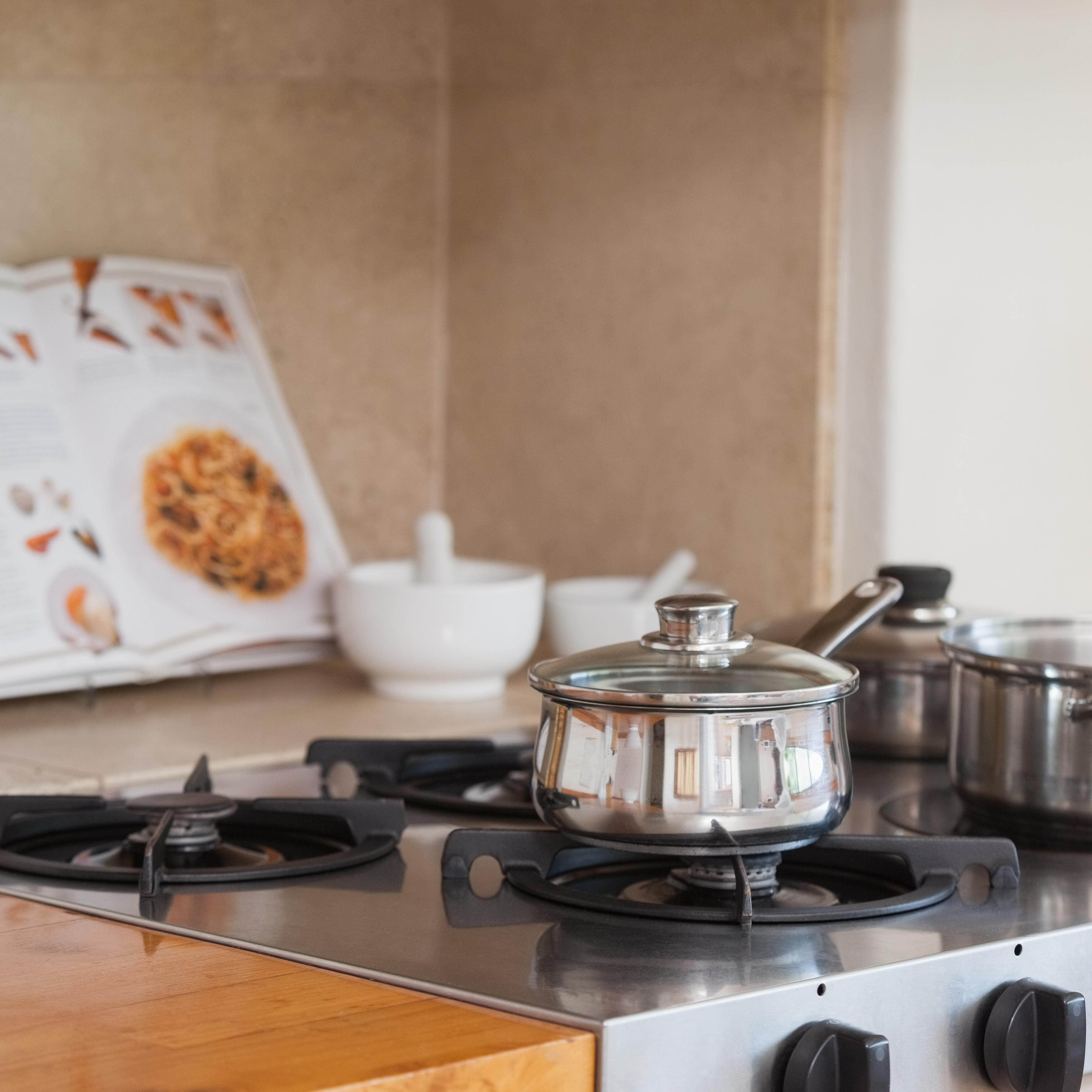 """""""Stove top with saucepan and recipe book"""" stock image"""