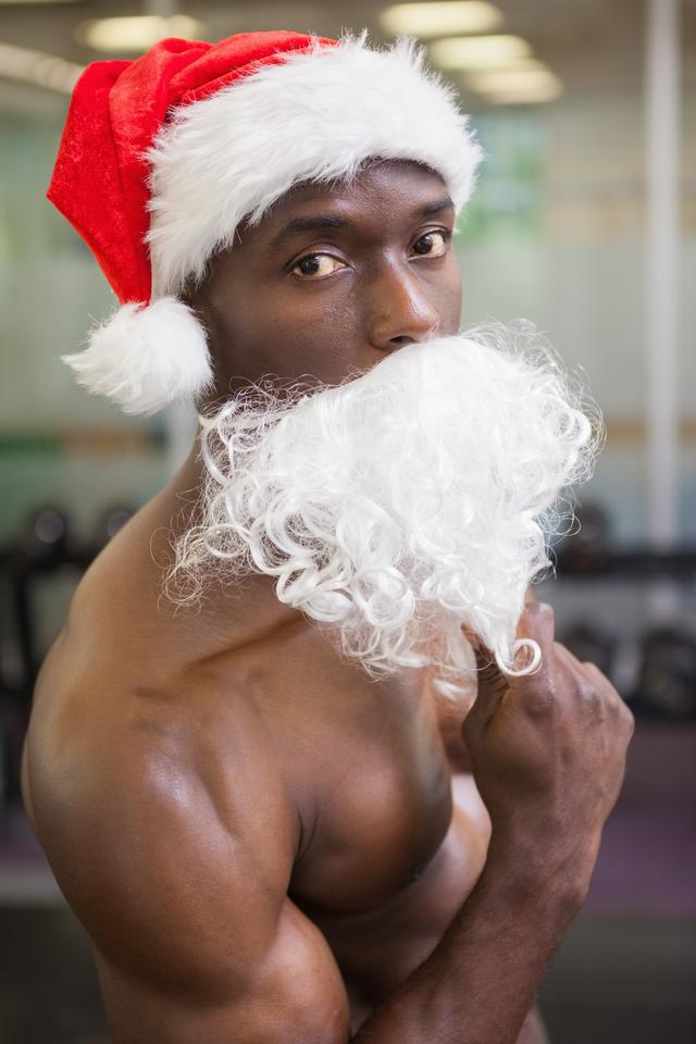 """Portrait of shirtless macho man in santa hat"" stock image"