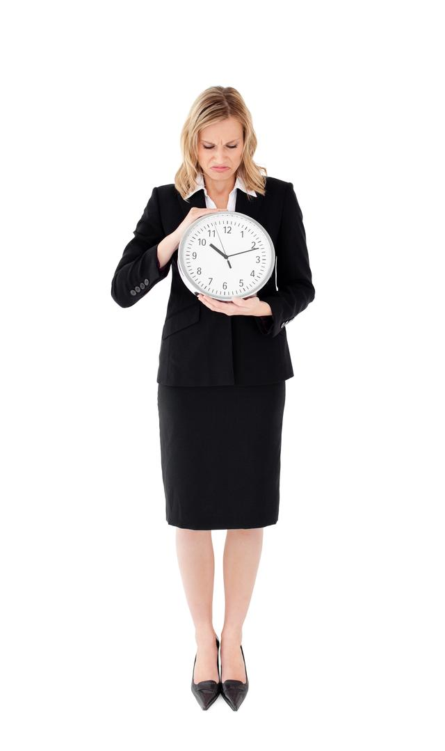"""Glum businesswoman holding a clock against white background"" stock image"