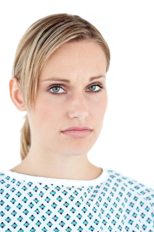 """Upset female patient against a white background"" stock image"