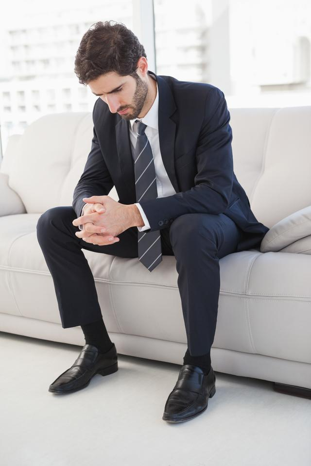 """Nervous businessman sitting on couch"" stock image"