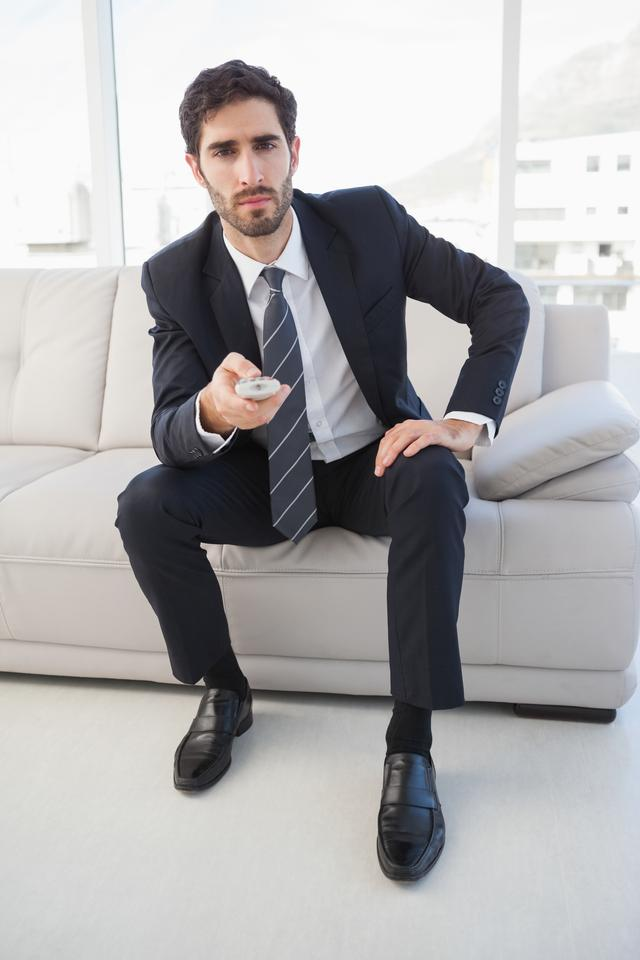 """Businessman holding a tv remote"" stock image"