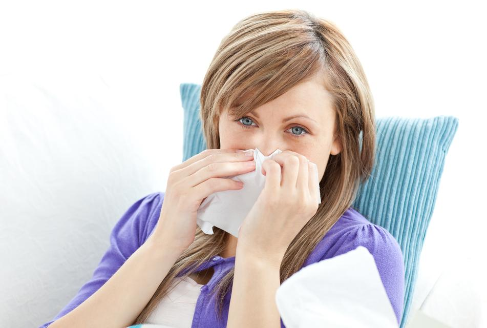 """""""Portrait of a sick pretty woman blowing lying on a sofa against white background"""" stock image"""