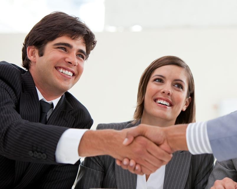 """""""Smiling businessman and his colleague closing a deal with a partner"""" stock image"""