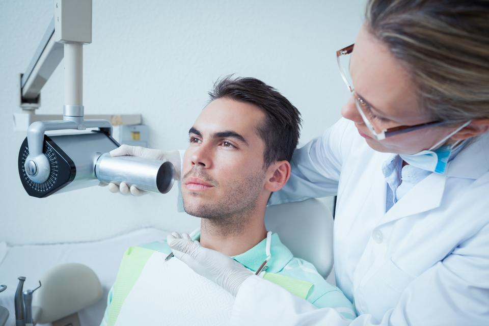 """""""Serious young man undergoing dental checkup"""" stock image"""
