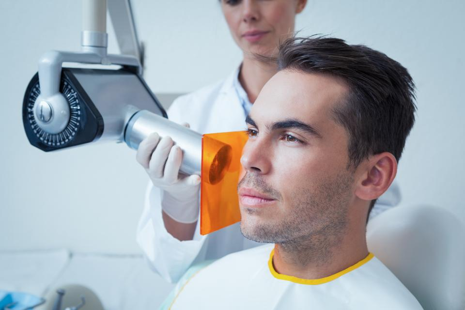 """Serious young man undergoing dental checkup"" stock image"