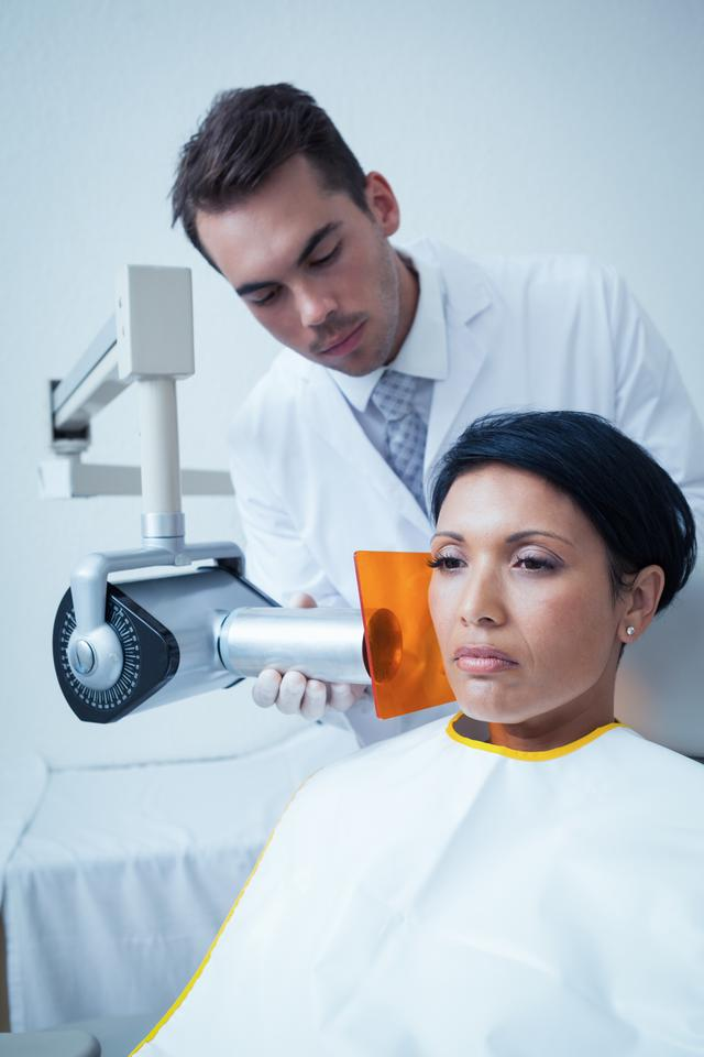 """Serious young woman undergoing dental checkup"" stock image"