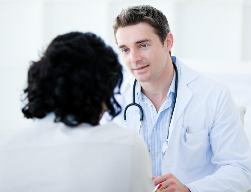 """""""Handsome doctor talking with his patient for the annual checkup"""" stock image"""
