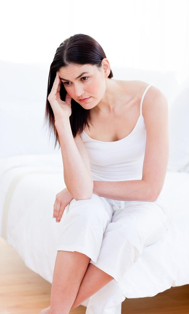 """Portrait of a unhappy woman sitting on bed"" stock image"