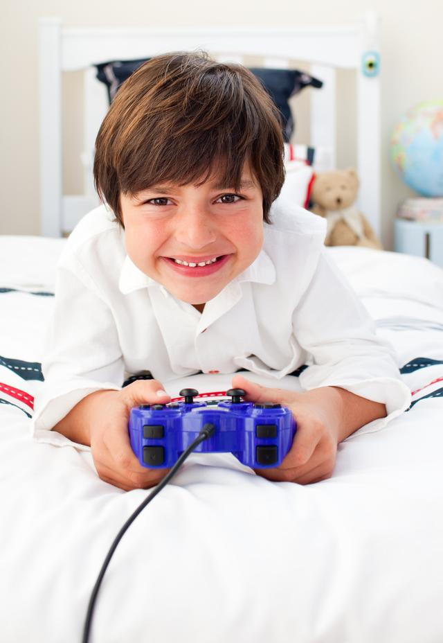 """Happy boy playing video games"" stock image"