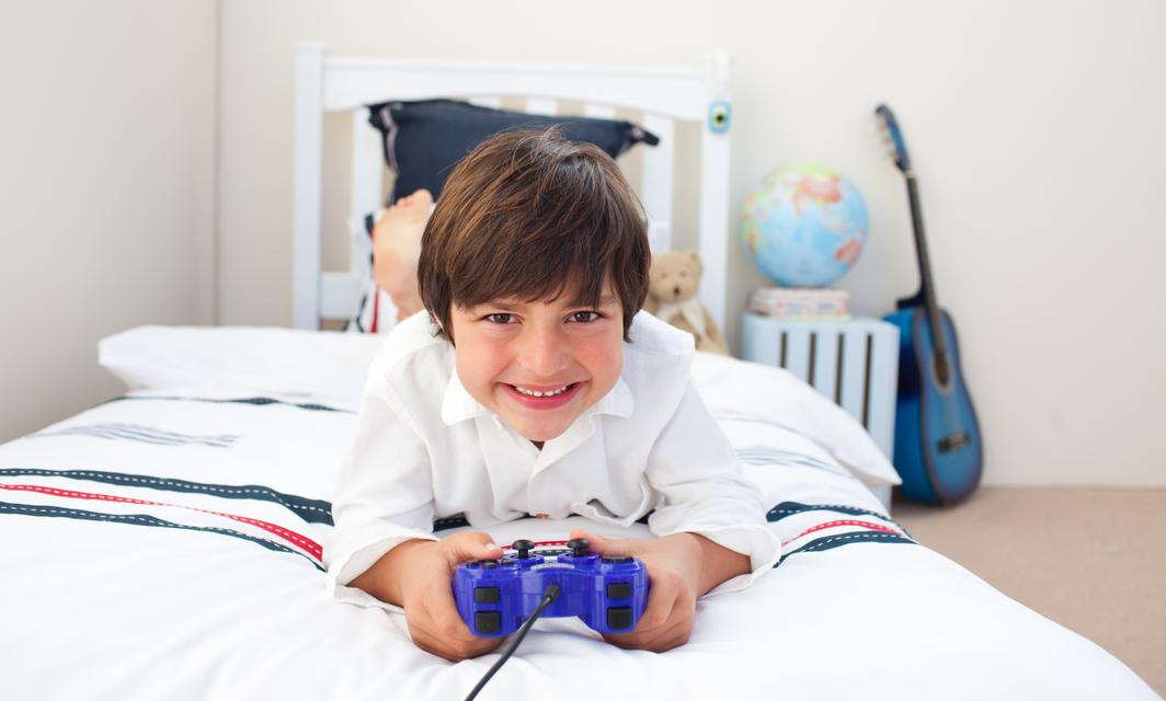 """Cute little boy playing video games"" stock image"