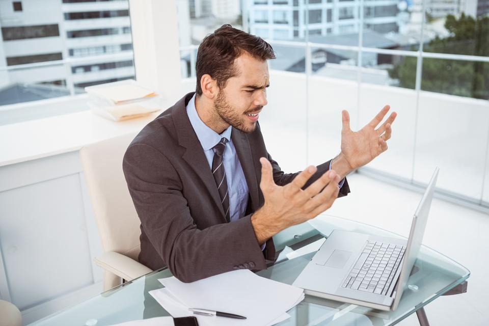 """Frustrated businessman using laptop in office"" stock image"