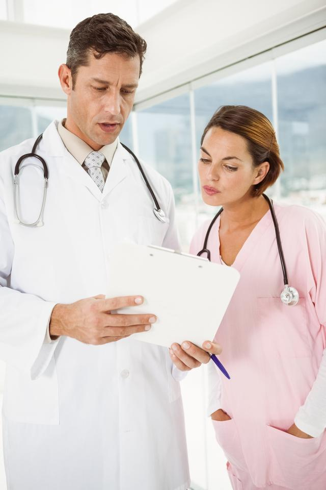 """""""Doctors discussing reports at medical office"""" stock image"""