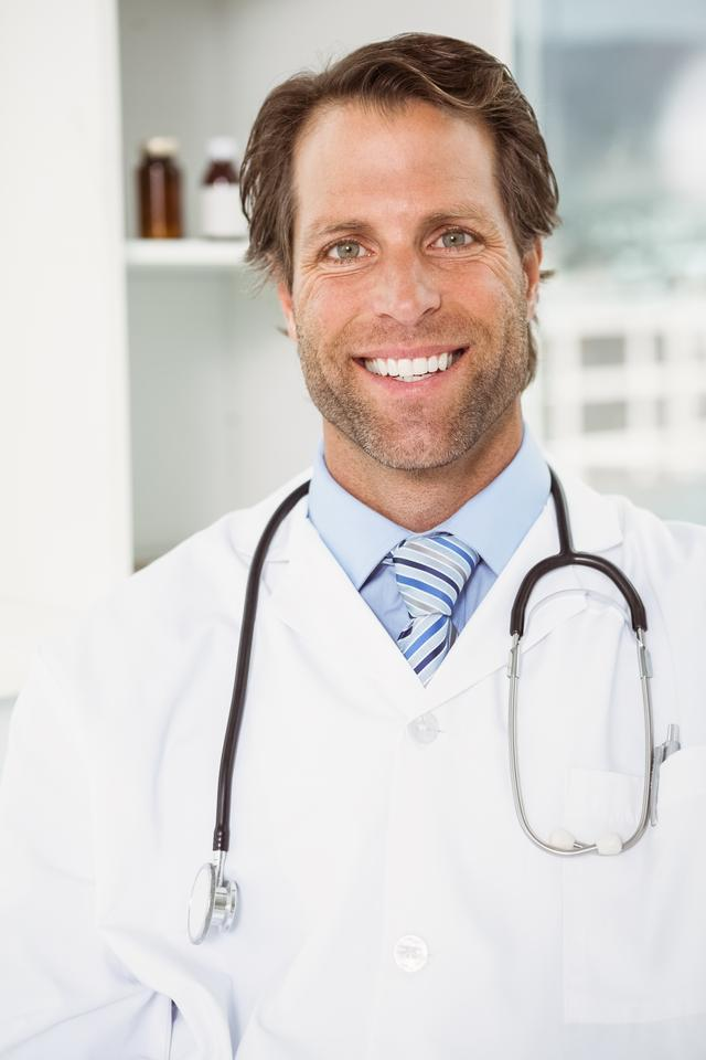 """""""Smiling male doctor in medical office"""" stock image"""