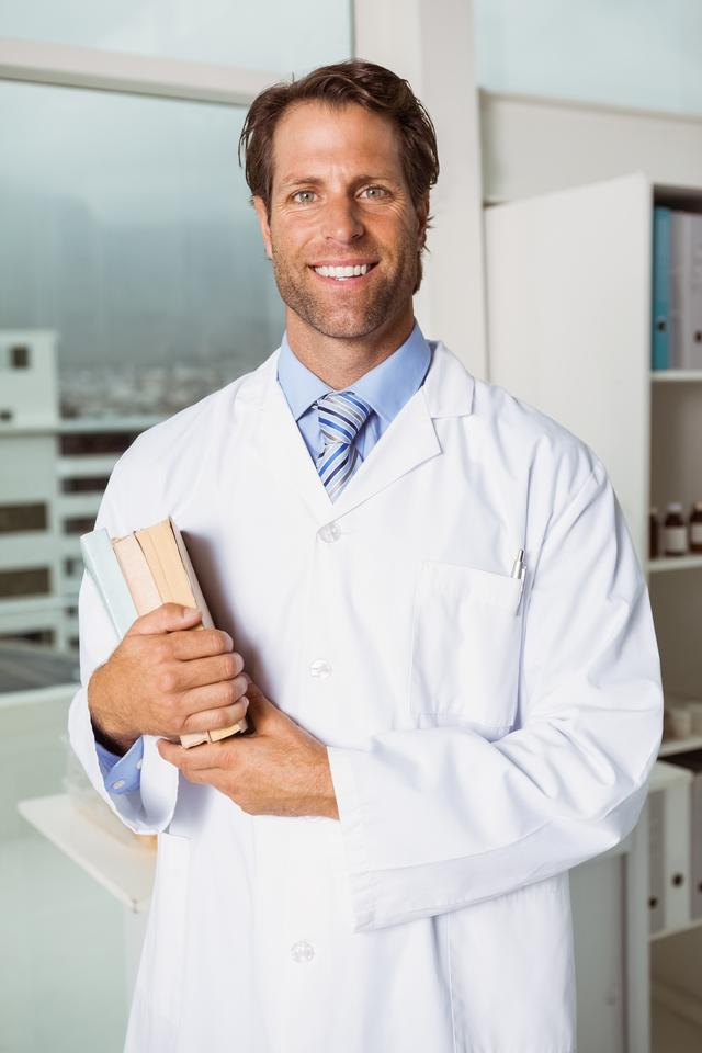 """""""Smiling male doctor holding books in medical office"""" stock image"""