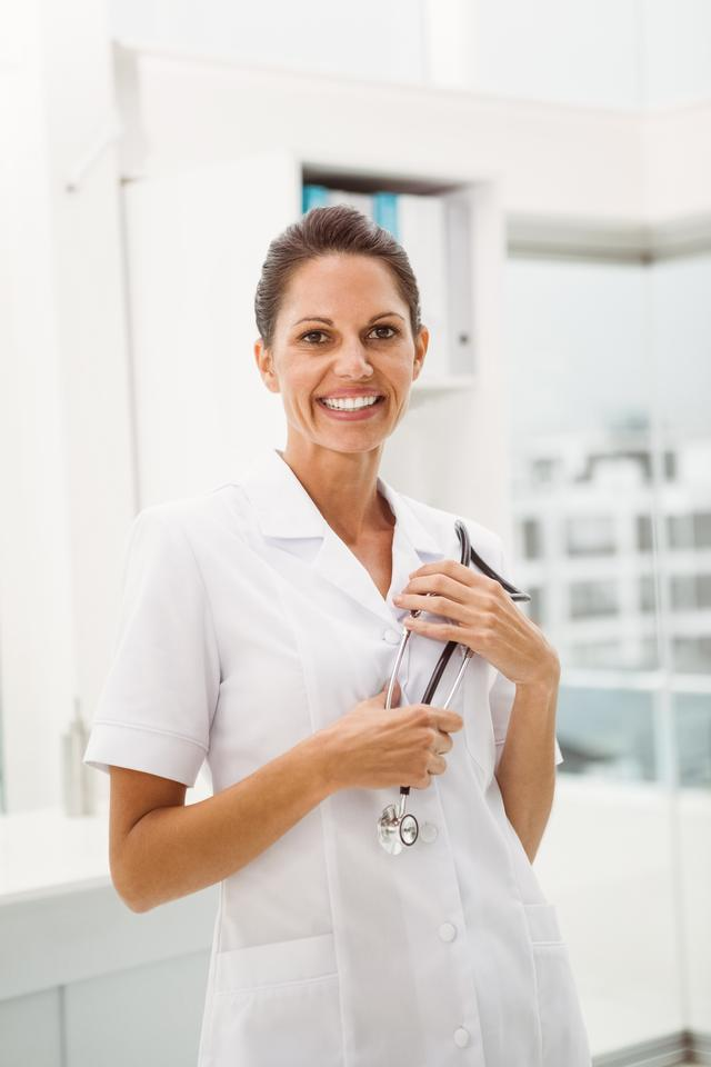 """""""Smiling female doctor with stethoscope at medical office"""" stock image"""