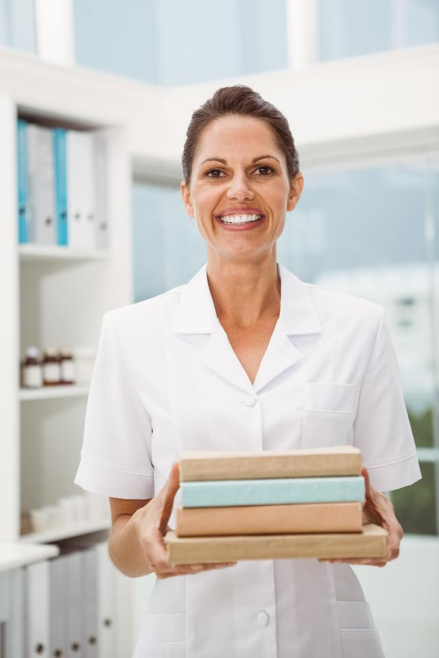"""""""Smiling female doctor holding books in medical office"""" stock image"""