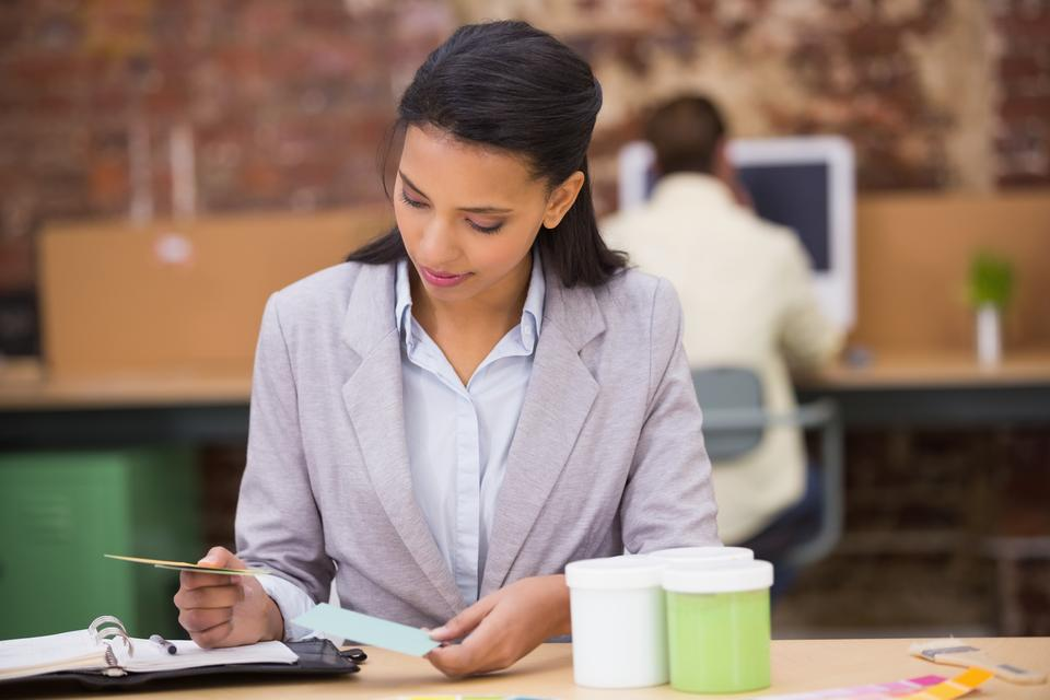 """Businesswoman looking at diary in office"" stock image"