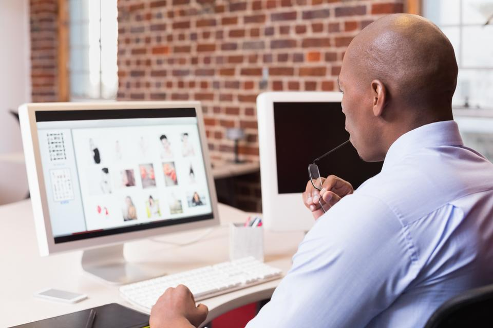 """""""Businessman looking at computer monitor in office"""" stock image"""