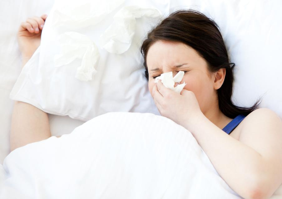 """""""Sick young woman using a tissue lying in a bed"""" stock image"""