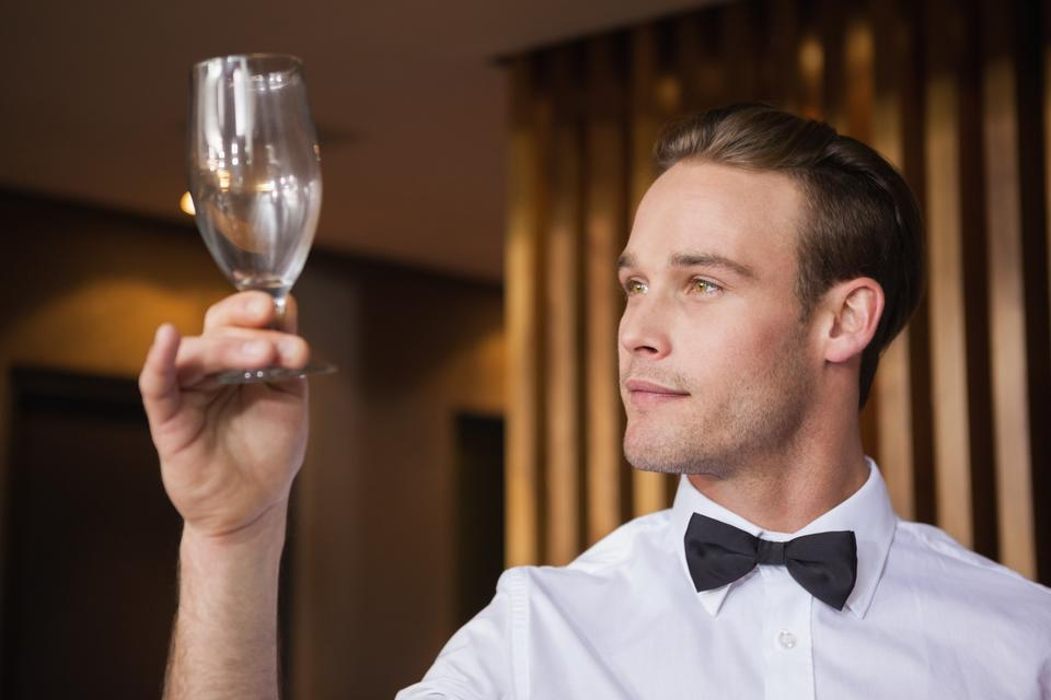 """""""Handsome waiter inspecting a wine glass"""" stock image"""