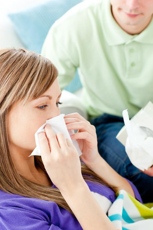 """""""Sick woman with tissue lying on a sofa"""" stock image"""