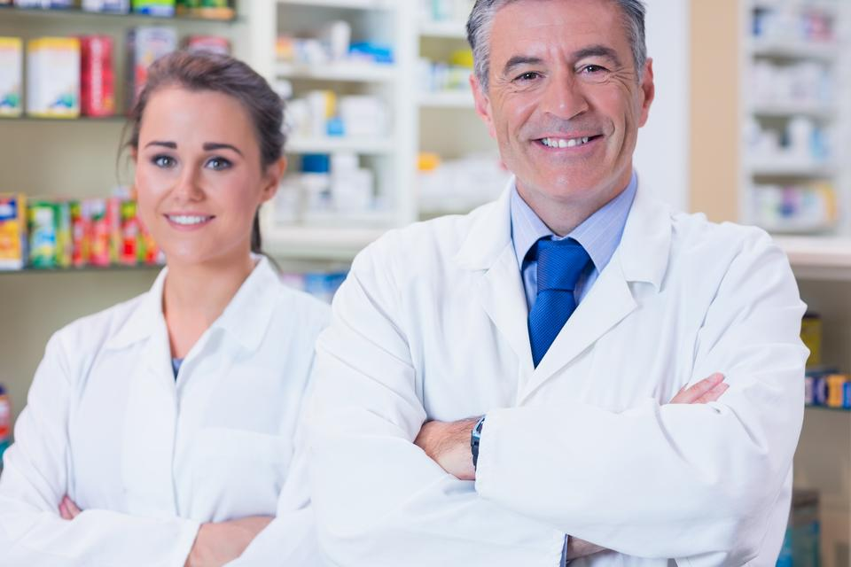 """Smiling pharmacist and his trainee with arms crossed"" stock image"