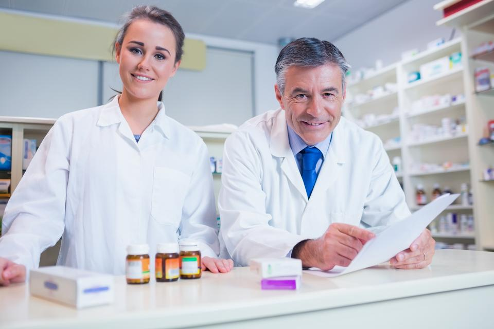 """Pharmacist holding a prescription next to his trainee"" stock image"
