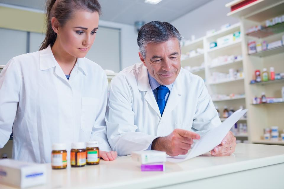 """Pharmacist showing a prescription to his trainee"" stock image"