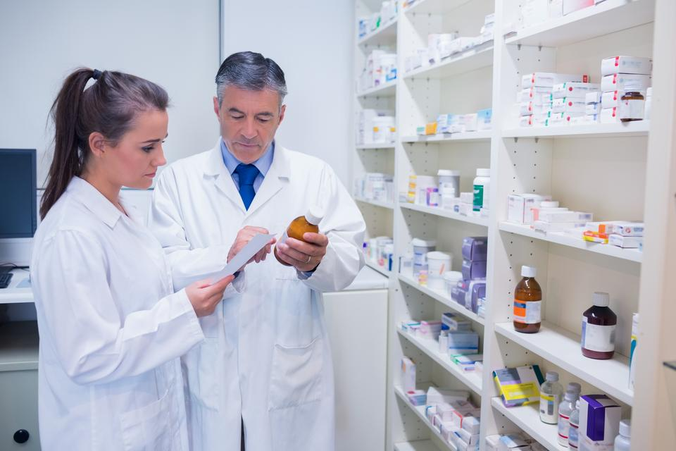 """Pharmacist and trainee talking together about medication"" stock image"