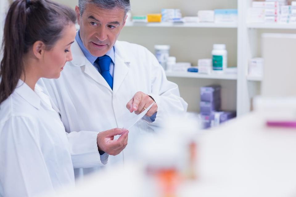 """Pharmacist explaining a prescription to his trainee"" stock image"