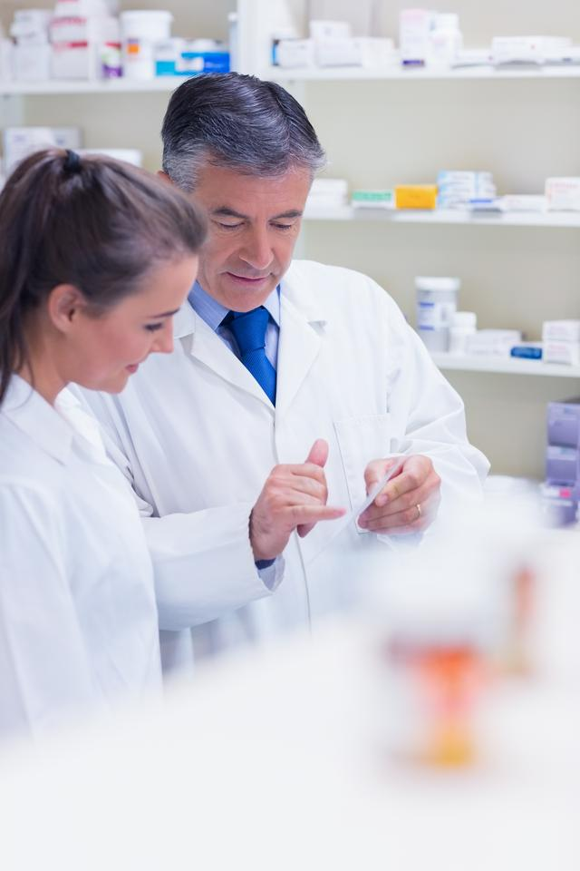 """Pharmacist speaking with his trainee about prescription"" stock image"