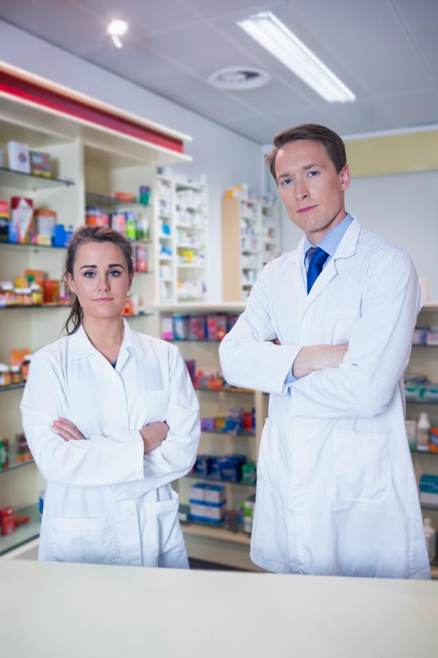 """Pharmacist and his trainee standing with arms crossed"" stock image"