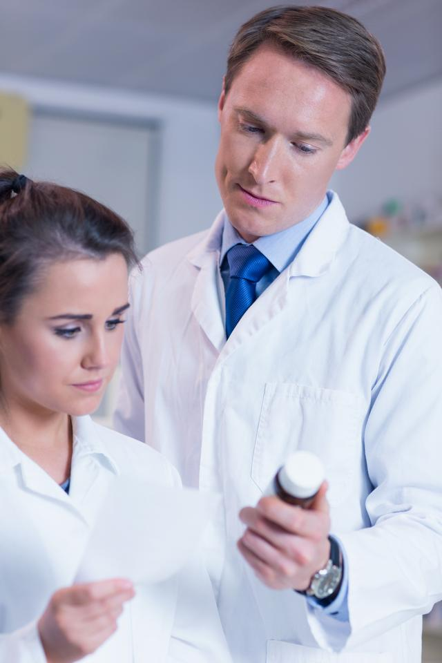 """Pharmacist showing medication to his trainee"" stock image"