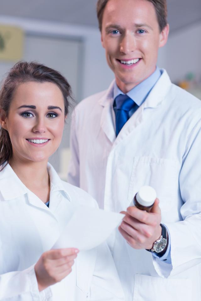 """Pharmacist and his trainee looking at the camera"" stock image"